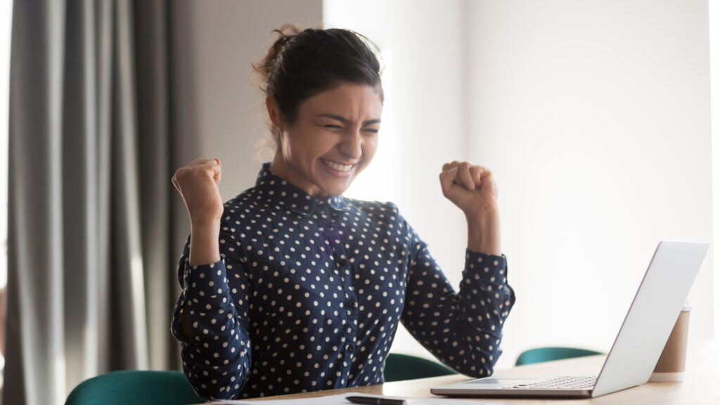 Excited happy indian employee celebrating success
