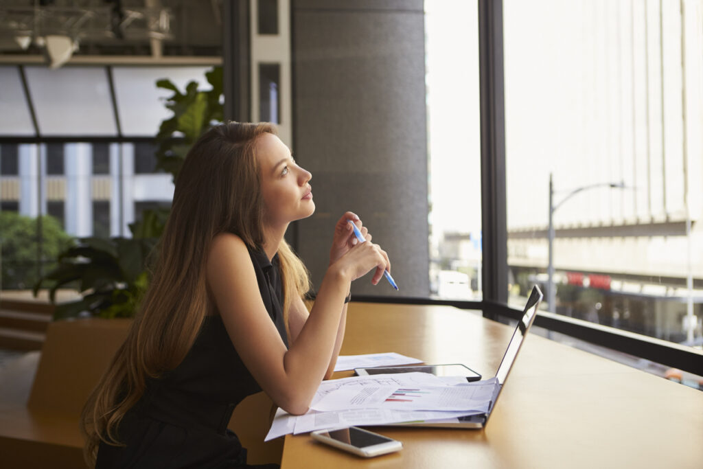 Woman thinking about how to improve her post purchase email campaigns.